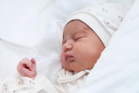 Neugeborenes Mädchen schlafen in ihrem Bett in der Entbindungsklinik