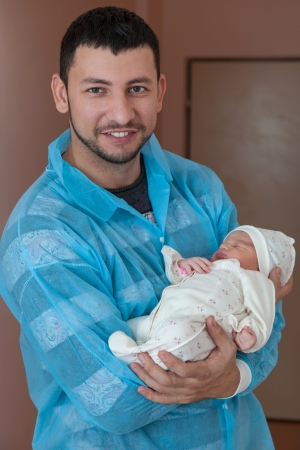 Happy father holding a baby in the maternity ward photo