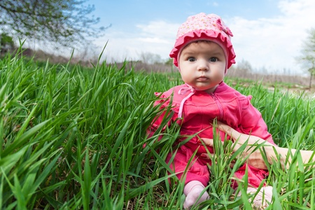 maternal: Baby in a pink suit sits among green grass supported maternal hand outdoors