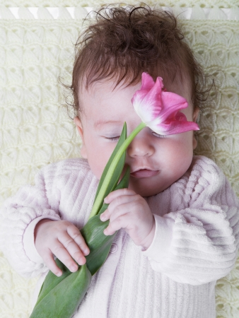 Portrait of a sleeping baby with a tulip flower Stock Photo