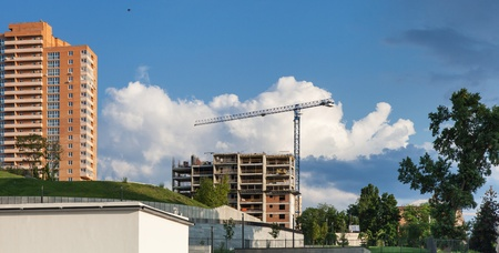 concrete commercial block: Construction site with crane and a new building on a background of sky with clouds in Kiev