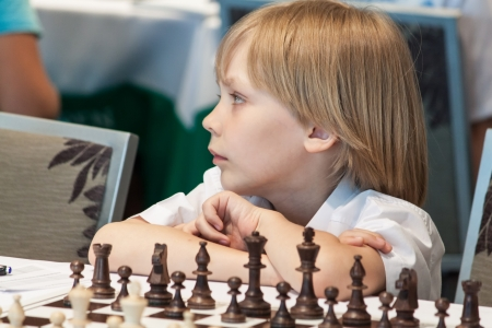 Young boy playing chess on the competitions photo