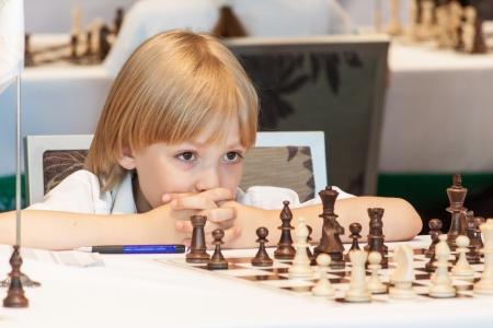 Junge spielt Schach auf den Wettkämpfen Standard-Bild