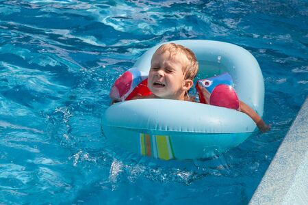 Small boy is afraid to swim in the pool Stock Photo