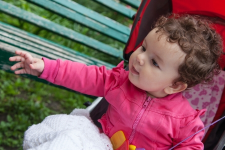 carefully: Portrait of baby girl sitting in stroller outdoors