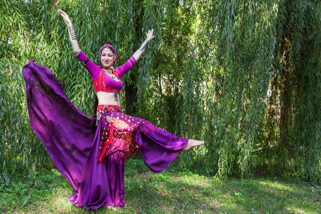 Dancer wearing oriental costume dancing in park photo
