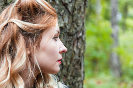 Profile of a young woman against a tree Stock Photo - 22760299