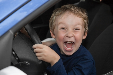Young boy is happy behind wheel of car