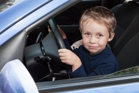 Young boy is happy behind wheel of car