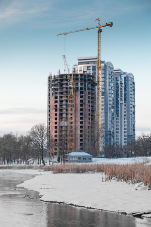Unfinished building on the river bank in winter photo