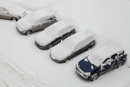 Cars covered by snow after snowstorm, top view photo
