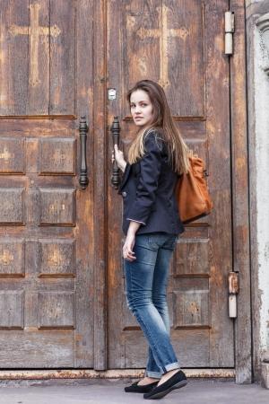 Junge Frau öffnet Tür der Kirche