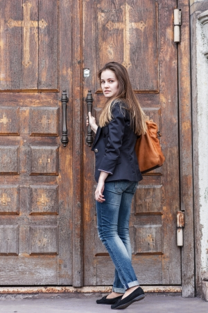 Young woman opens door of the church