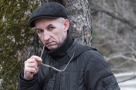 Portrait of pensive man in cap outdoor