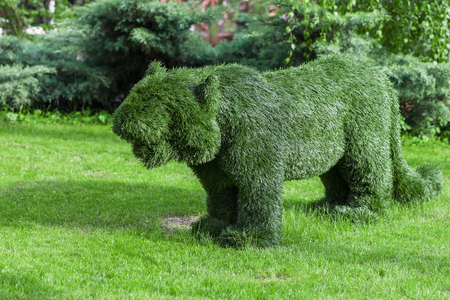 Figure pumas made ​​of synthetic mimics trimmed bush photo