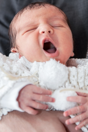 Yawning baby at the hands of his father
