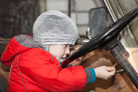Boy puts the key into the ignition lock, playing in the old car, focus on the hand with key photo