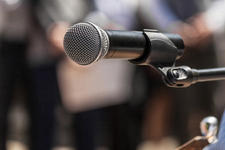 hablar en publico: Micrófono en el fondo figuras borrosas de personas durante una manifestación de cerca