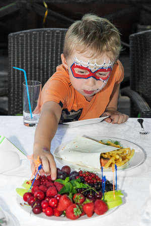 Young boy with painted face reaching for fruit photo