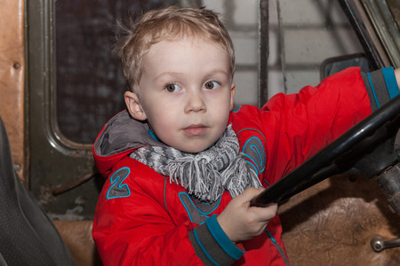 Boy playing behind the wheel of an old car photo