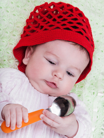 Portrait baby in red bonnet with spoon in hand photo