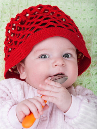 playing with spoon: Portrait baby in red bonnet with spoon in hand