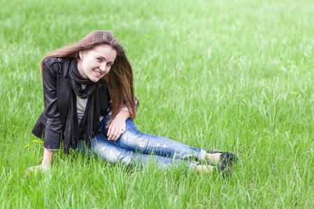 Beautiful young woman sits on a green lawn