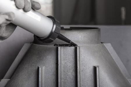 close fitting: Chimney installation on modern cast iron fireplace, applying sealant