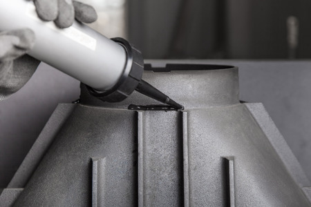 Kamin Installation auf modernen Gusseisen Kamin, Auftragen der Dichtmasse