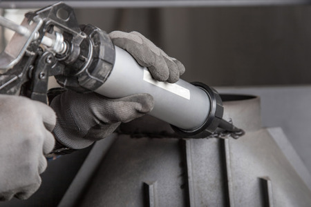 Chimney installation on modern cast iron fireplace, applying sealant