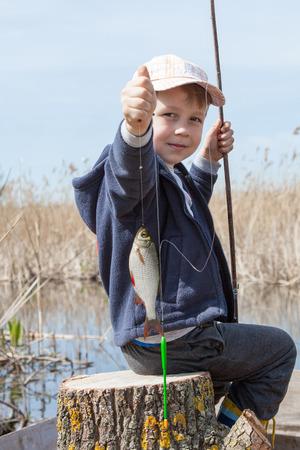 Gelukkige jongen die een vis gevangen in de vijver Stockfoto