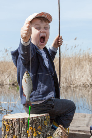 Happy boy holding a fish caught in the pond photo