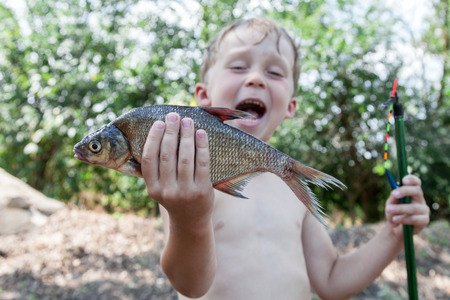 The young fisherman with the fish bream caught