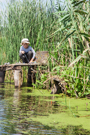 Junge Angler fängt einen Fisch am Angelgerät
