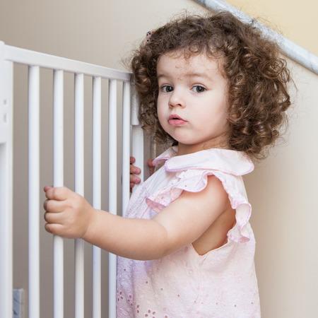 Portrait of a cute curly-hair girl near stair gate Foto de archivo
