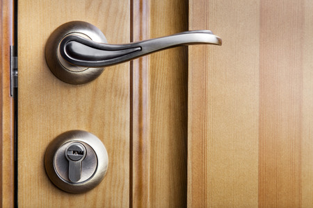 Modern style door handle on natural wooden door Фото со стока - 35343670