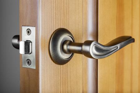 Slightly opened wooden door with latch handle closeup