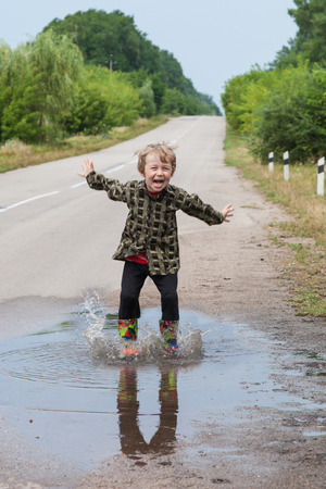Junge springt in Pfützen auf der Landstraße Standard-Bild