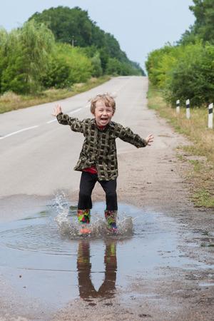 Junge springt in Pfützen auf der Landstraße Lizenzfreie Bilder