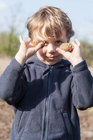 hellion: The boy shows sprouted of potatoes tubers