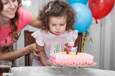 Two year old baby girl blows out candles on cake on his birthday, her happy mom in the background Stock Photo
