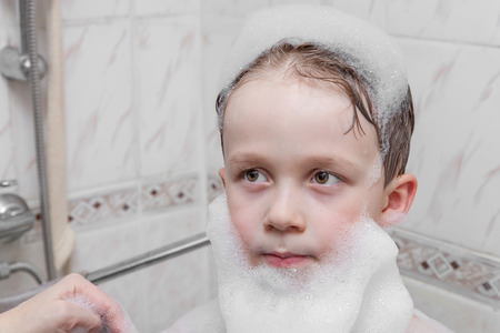soap suds: Young boy in the bathroom with beard and cap of soap suds