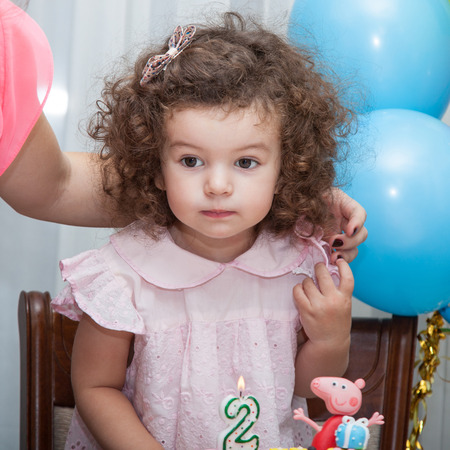two year: Two year old baby girl blows out candles on cake on his birthday Stock Photo