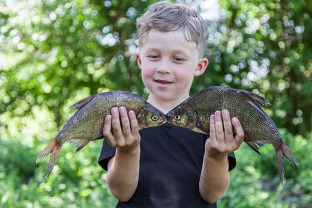 Glücklicher Junge Fischer hält zwei Fische Brassen an der Köder Lizenzfreie Bilder