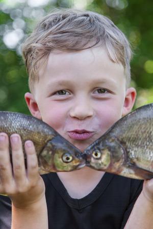 Glücklicher Junge Fischer hält zwei Fische Brassen an der Köder Standard-Bild - 41068016