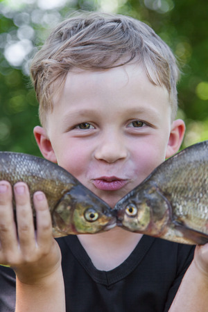 Happy boy fisherman holding two fish bream caught at the bait