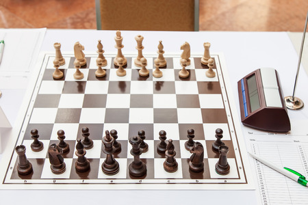 Chess board with wooden figures at the beginning of the chess tournament photo
