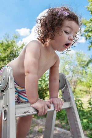 Baby girl standing on top stepladder outdoors