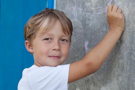 decide: El muchacho joven ni�o en edad preescolar para la escuela, decide ejemplos aritm�ticos Foto de archivo