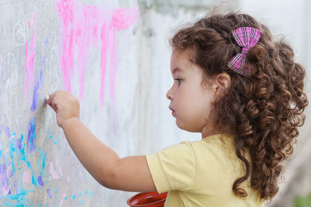 Curly cute baby girl drawing with chalk on the wall